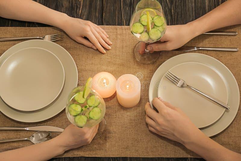 Júntese con los vidrios de agua fresca del pepino que cena romántico imagen de archivo