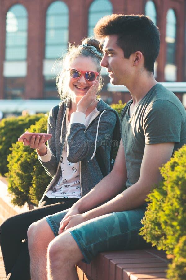 Júntese de los amigos, adolescente y muchacho, divirtiéndose así como smartphones imagenes de archivo
