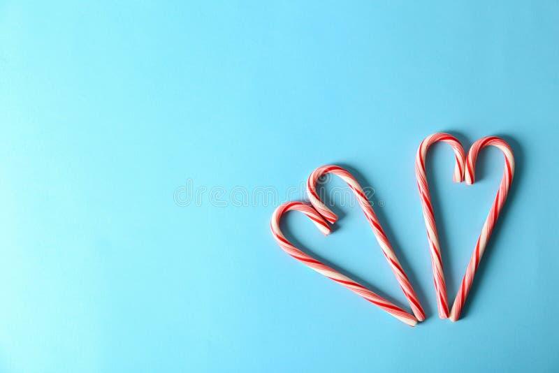 Júntese de los amores hechos con los bastones de caramelo en el fondo del color, visión superior imagen de archivo