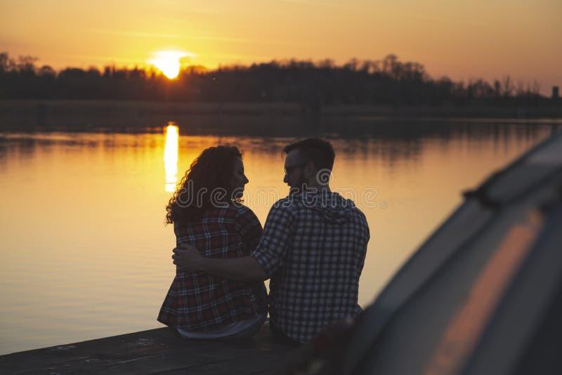 Júntese de los campistas que disfrutan de puesta del sol sobre el lago fotografía de archivo libre de regalías