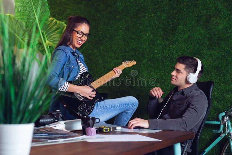 Júntese de los compañeros de trabajo que disfrutan de una cierta música en oficina Muchacha que toca la guitarra imagen de archivo
