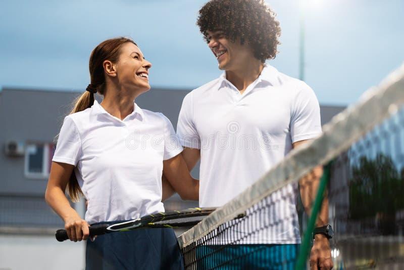 Júntese de los jugadores de tenis que sonríen en la corte después de un partido imagen de archivo libre de regalías