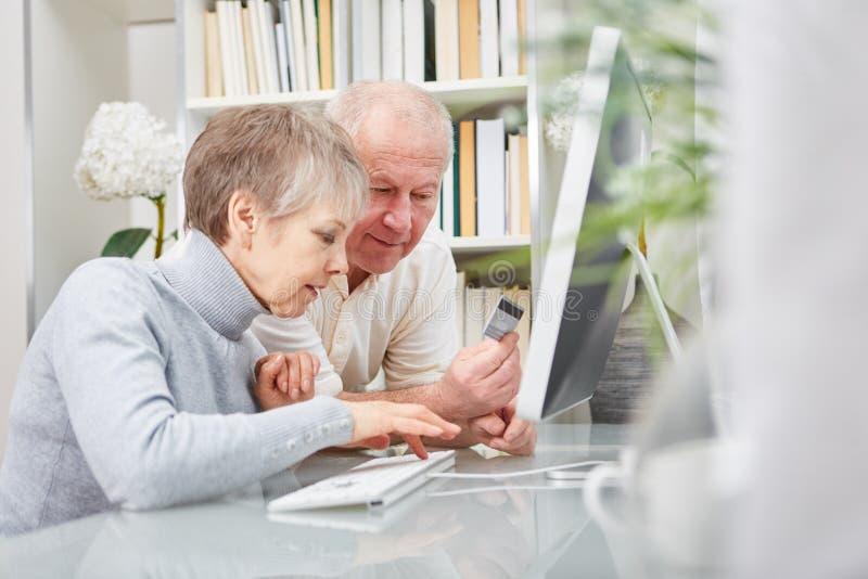 Júntese de los mayores que hacen compras en Internet fotos de archivo