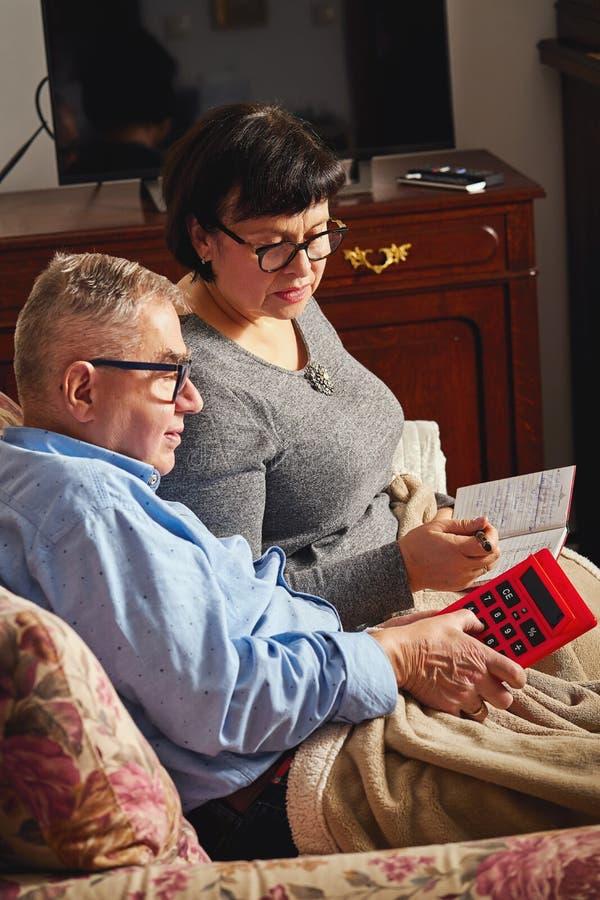 Júntese de los mayores que hacen la contabilidad del hogar con la calculadora y la planificación fotografía de archivo libre de regalías