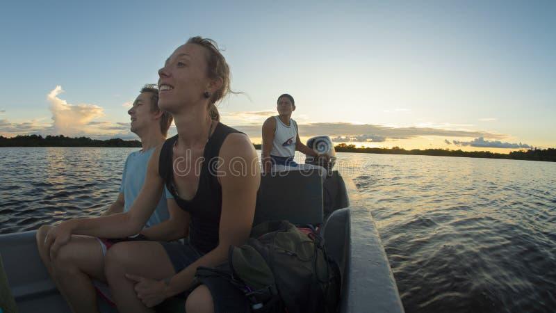 Júntese de los turistas que viajan en canoa en un río en el Amazonas mientras que admira la puesta del sol imagen de archivo libre de regalías