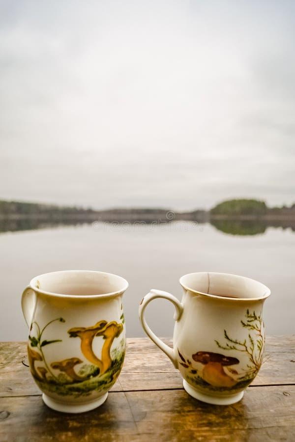 Júntese de tazas de té con la imagen de setas imagenes de archivo