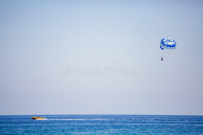 Júntese de turistas vuela en un paracaídas azul y blanco fotos de archivo