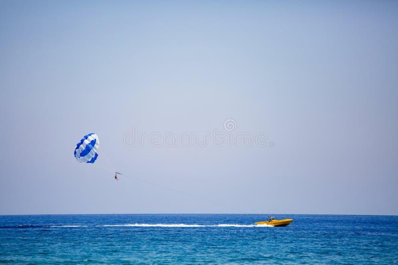 Júntese de turistas vuela en un paracaídas azul y blanco foto de archivo libre de regalías