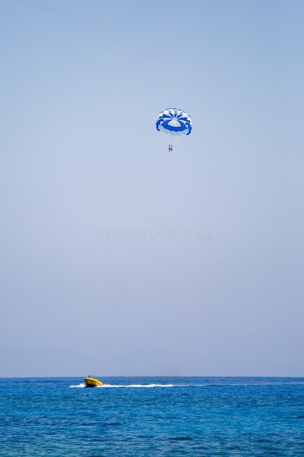 Júntese de turistas vuela en un paracaídas azul y blanco fotografía de archivo libre de regalías