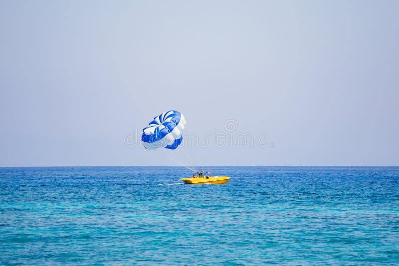 Júntese de turistas vuela en un paracaídas azul y blanco fotos de archivo libres de regalías