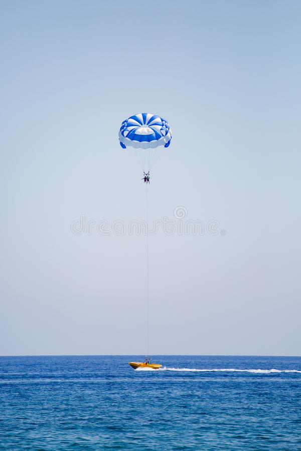 Júntese de turistas vuela en un paracaídas azul y blanco imagen de archivo