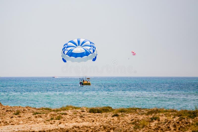 Júntese de turistas vuela en un paracaídas azul y blanco imágenes de archivo libres de regalías