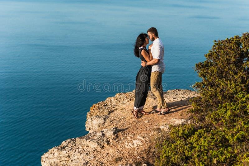 Júntese en el amor que abraza en una roca por el mar imágenes de archivo libres de regalías