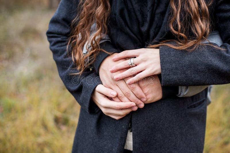 Júntese en el amor que camina en el parque del otoño que lleva a cabo las manos que miran en la puesta del sol imagen de archivo libre de regalías