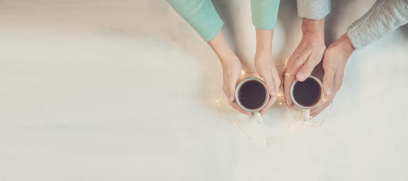 Júntese en el amor que lleva a cabo las manos con café en la tabla de mármol blanca, con las luces de la Navidad Fotografía tomad imagen de archivo