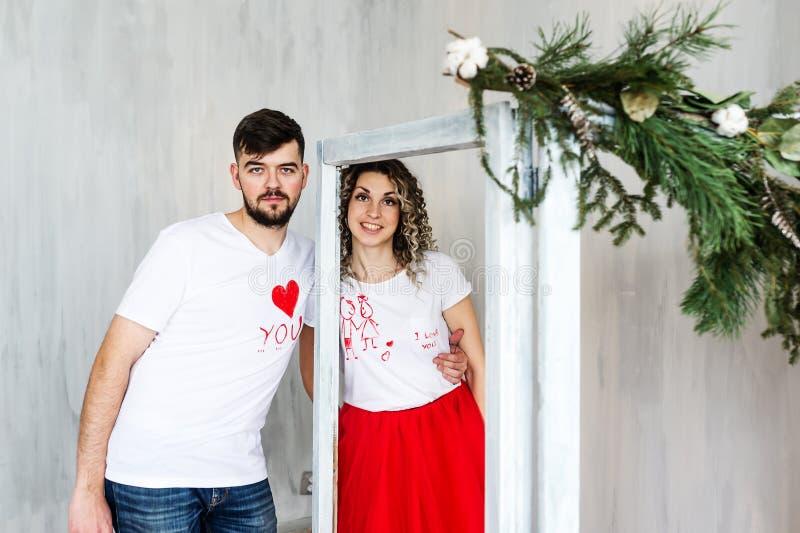 Júntese en el amor que se coloca al lado de una rama del abeto el día de tarjeta del día de San Valentín del St imagenes de archivo