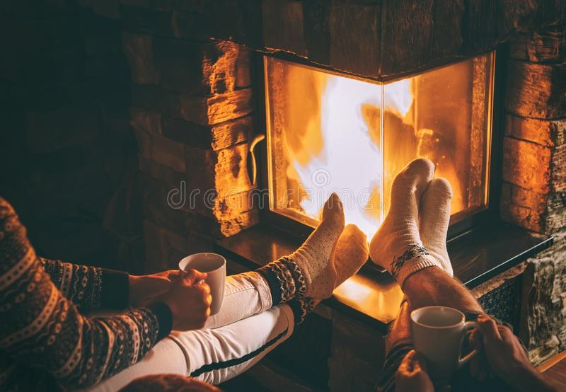 Júntese en el amor que se sienta cerca de la chimenea Piernas en calcetines calientes cerca foto de archivo libre de regalías