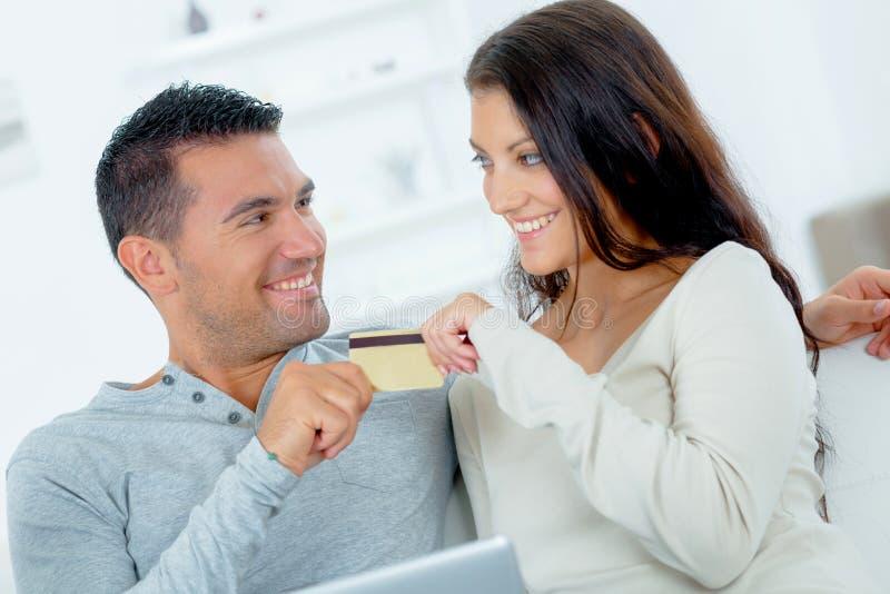 Júntese en el sofá ambos que agarran la misma tarjeta de crédito imagenes de archivo