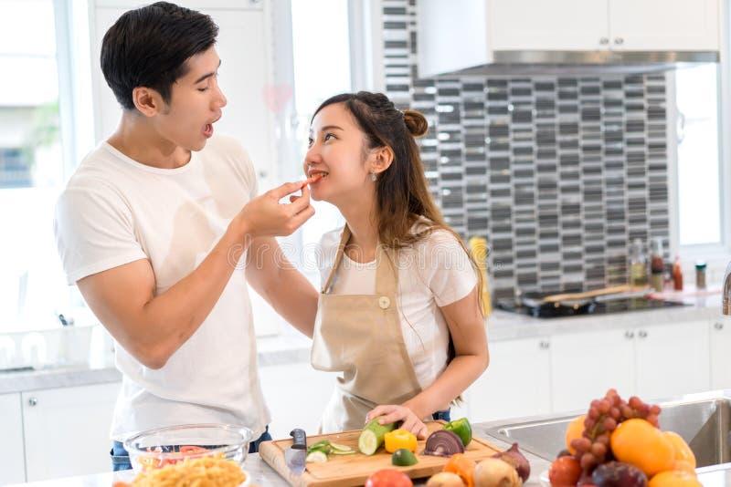 Júntese junto en el sitio de la cocina, hombre asiático joven que sostiene verduras a la mujer foto de archivo libre de regalías