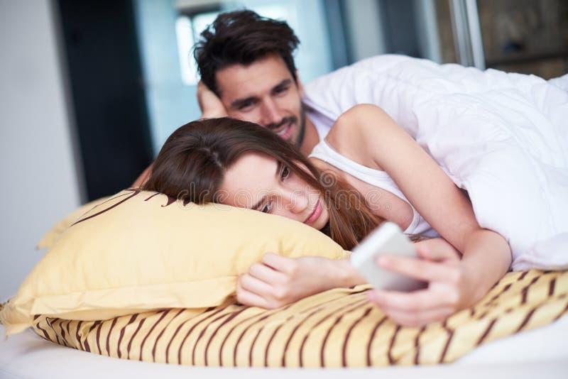 Júntese relajan y se divierten en cama imágenes de archivo libres de regalías