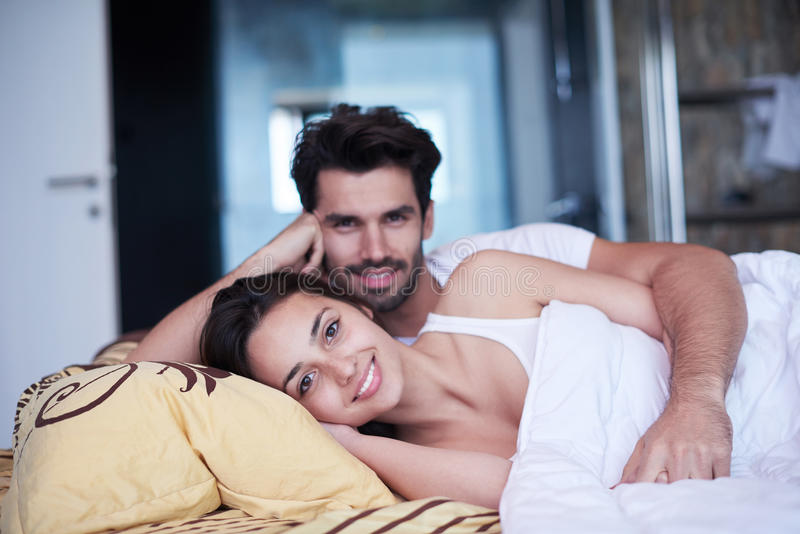 Júntese relajan y se divierten en cama foto de archivo