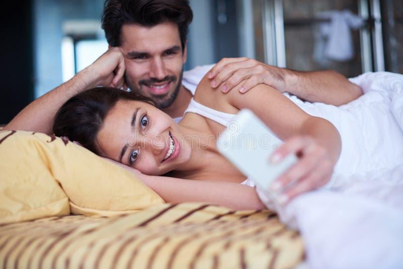 Júntese relajan y se divierten en cama fotografía de archivo