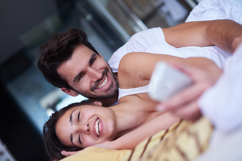 Júntese relajan y se divierten en cama fotos de archivo