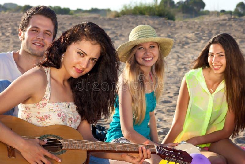 Júntese y dos amigos femeninos que se sientan en la playa que juega guita imagen de archivo