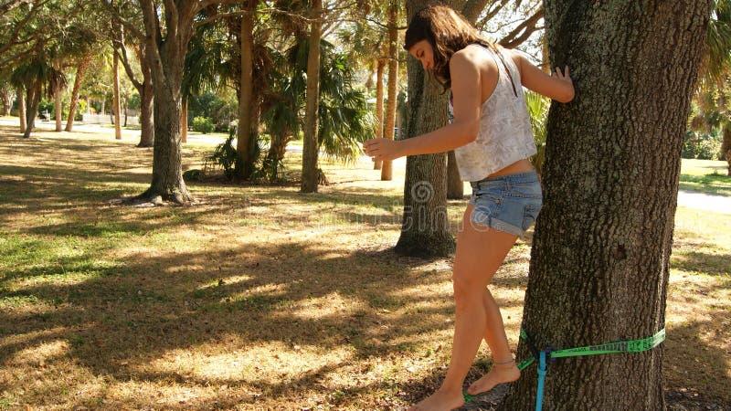 JÚPITER, FLORIDA EUA - 17 DE JUNHO DE 2017 Jovem mulher que faz o slackline praticando em um parque público em Florida imagens de stock royalty free