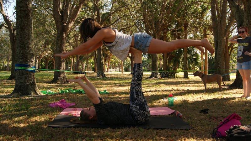 JÚPITER, FLORIDA EUA - 17 DE JUNHO DE 2017 Jovens mulheres que fazem a ioga & o slackline do acro em um parque público em Florida foto de stock royalty free