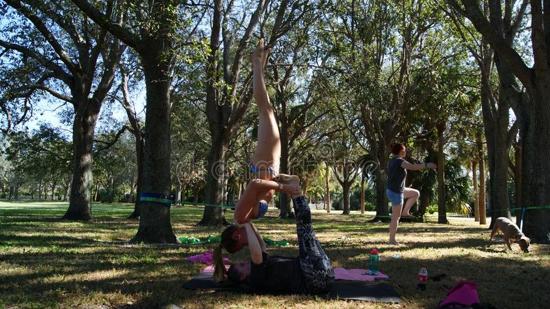 JÚPITER, FLORIDA EUA - 17 DE JUNHO DE 2017 Jovens mulheres que fazem a ioga & o slackline do acro em um parque público em Florida imagens de stock royalty free