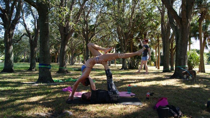 JÚPITER, FLORIDA EUA - 17 DE JUNHO DE 2017 Jovens mulheres que fazem a ioga & o slackline do acro em um parque público em Florida fotografia de stock royalty free