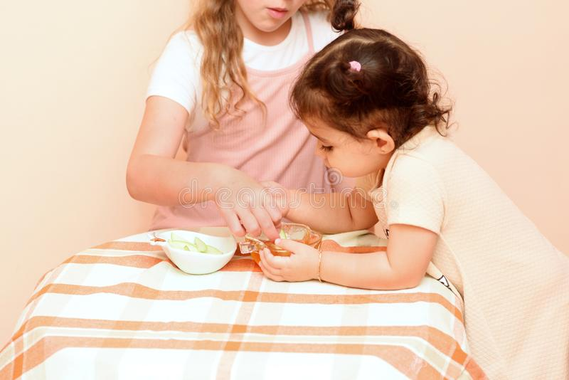 Jüdische Kinder, die Apfelscheiben in Honig auf Rosh HaShanah eintauchen lizenzfreie stockfotografie
