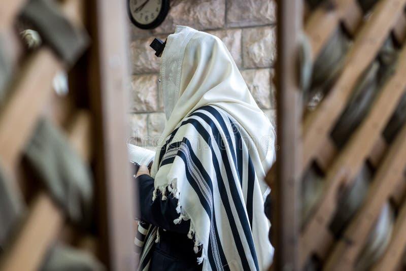 Jüdische Männer, die in einer Synagoge mit Tallit beten lizenzfreie stockbilder