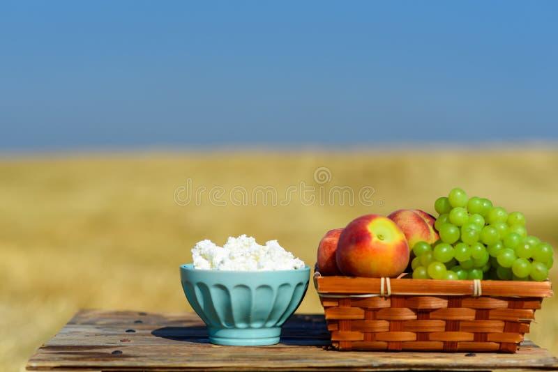 Jüdischer Feiertag Shavuot, Erntefest Hüttenkäse und Obstkorb auf Holztisch über Wiesen- und Himmelhintergrund stockfotos