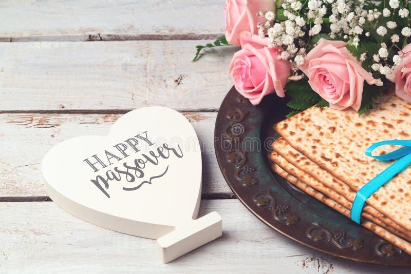 Jüdisches Feiertag Passahfest Pesah-Konzept mit Matzoh, rosafarbene Blumen und Herzform unterzeichnen vorbei hölzernen Hintergrun stockfotografie