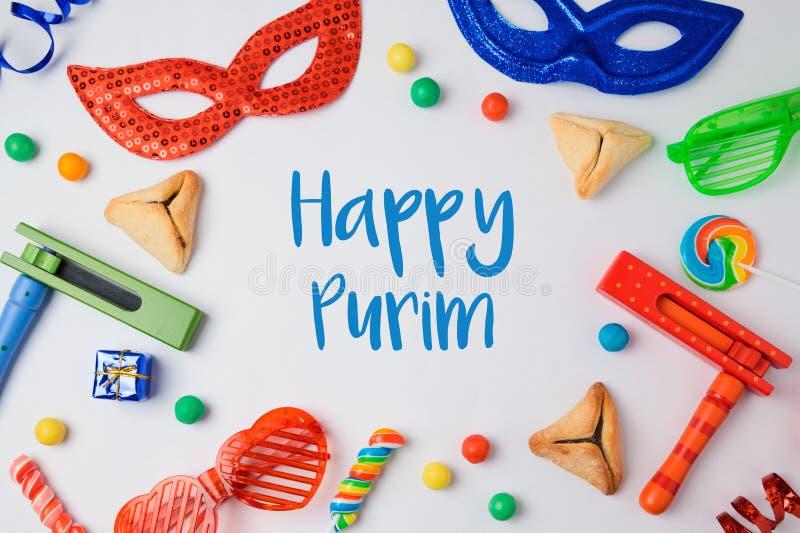 Jüdisches Feiertag Purim-Konzept mit hamantaschen Plätzchen, Karnevalsmaske und Krachmacher auf weißem Hintergrund stockfotografie