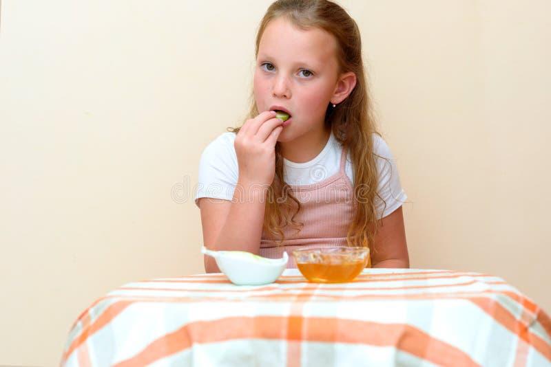 Jüdisches Kind, das Apfelscheiben in Honig auf Rosh HaShanah eintaucht stockfoto