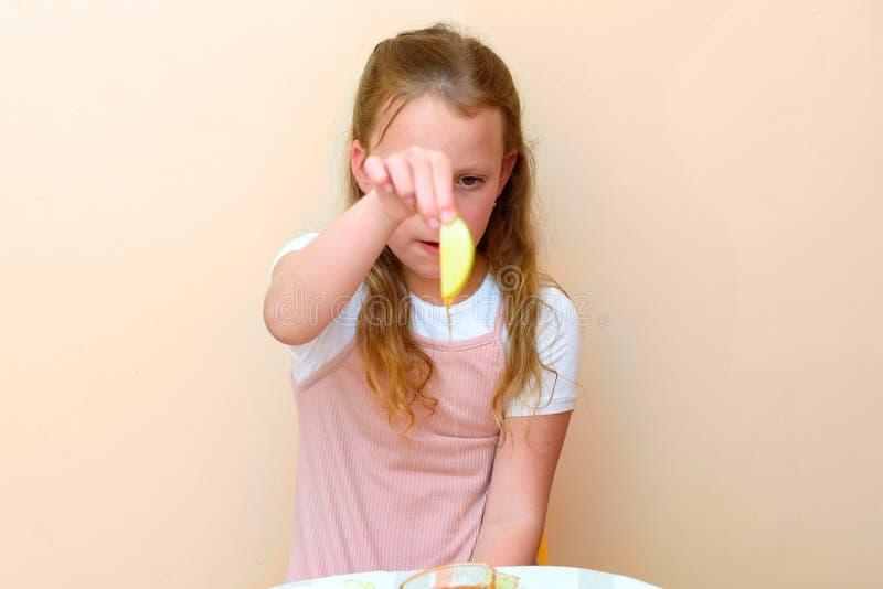 Jüdisches Kind, das Apfelscheiben in Honig auf Rosh HaShanah eintaucht lizenzfreies stockbild