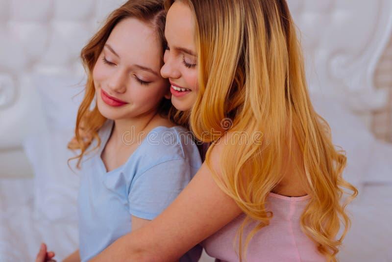 Jüngere Schwester, die gestützt und mit ihren älteren Geschwister glücklich sich fühlt stockfoto
