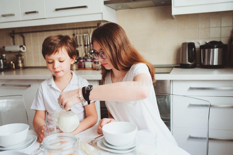 Jüngerer Bruder und jugendlich Schwester, die zu Hause in der modernen weißen Küche frühstücken und Snäcke essen lizenzfreie stockfotos