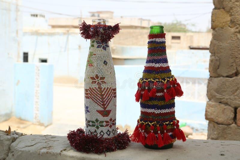 Języka nowoindoaryjskiego rzemieślnika rękodzieła: z paciorkami colourful obudowy dla butelek fotografia stock