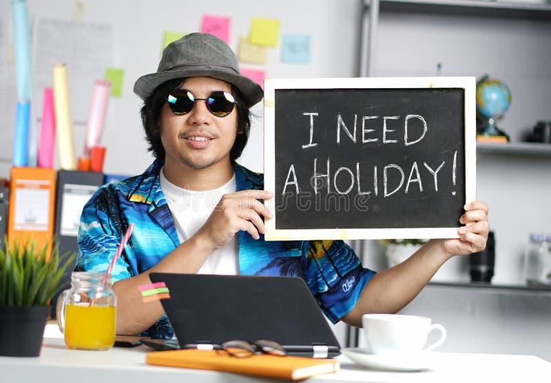 J'ai besoin d'un concept de vacances Jeune homme tenant le tableau noir vide Whi photographie stock libre de droits
