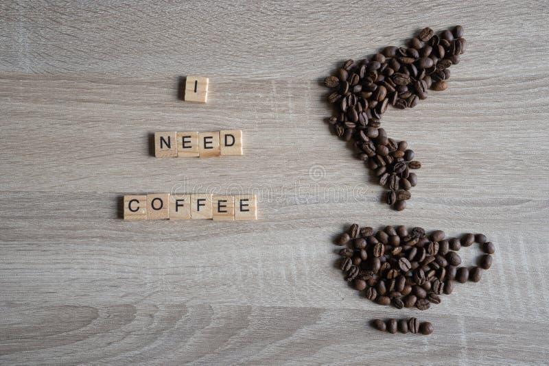 J'ai besoin du qoute de mot de café avec les grains de café rôtis placés dans photos libres de droits