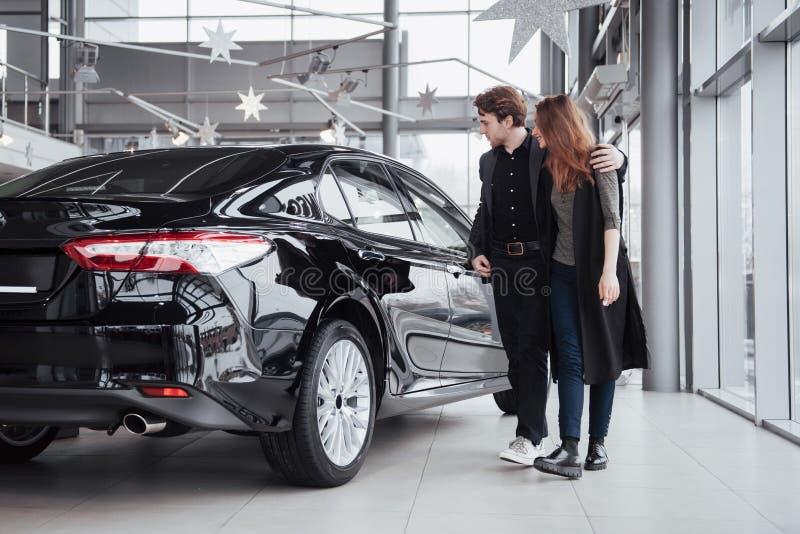 J'aime cette voiture Beaux jeunes couples se tenant au concessionnaire choisissant la voiture pour acheter photos stock