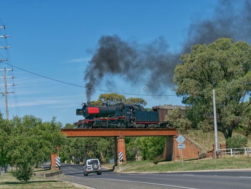 J de Locomotief die van de Klassenstoom een wegbrug op de Victoriaanse Goudveldenspoorweg kruisen royalty-vrije stock foto