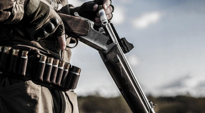 J?gareman Jaga period Man med ett vapen, gev?r Mannen laddar ett jaktgev?r Process av jakt under jakt arkivfoton