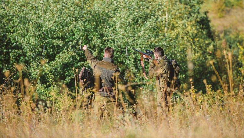 J?gerfreunde genie?en Freizeit Teamwork und Unterst?tzung T?tigkeit f?r wirkliches Mannkonzept J?ger mit Gewehren in der Natur stockbild