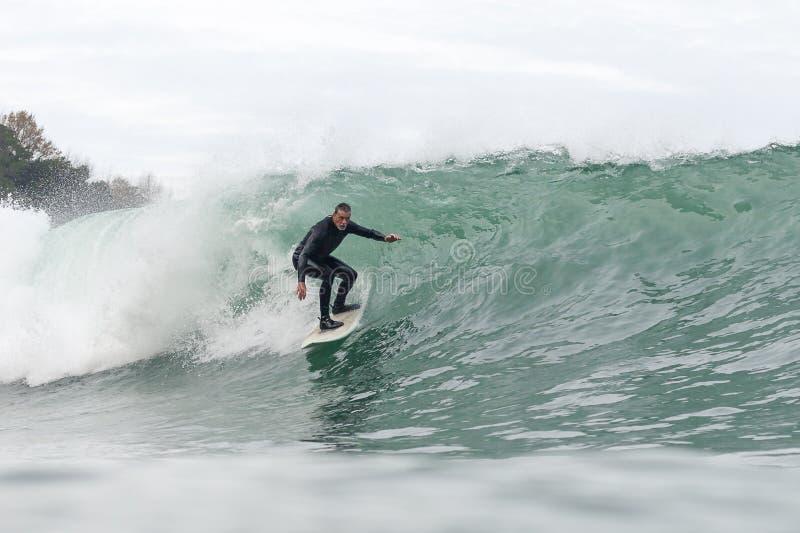 j?hriger Mann 68, der eine gro?e Welle surft stockfotografie
