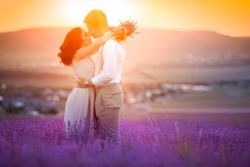 J?ntese de amantes en brillantemente el verano que mira hacia fuera encendido a los campos de la lavanda que se detienen a mano V fotos de archivo